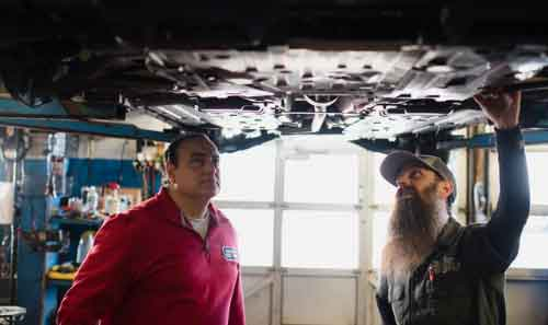 Ralph Parente de Soundview Service Center y Charles Sanville (conocido como The Humble Mechanic) examinan un auto en un elevador